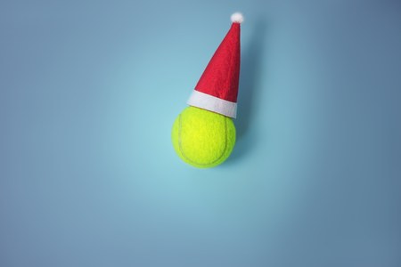 santa hat on tennis ball Christmas greeting Фото со стока