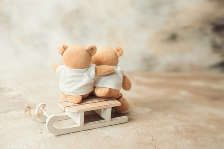 two teddy bears holding in ones arms
