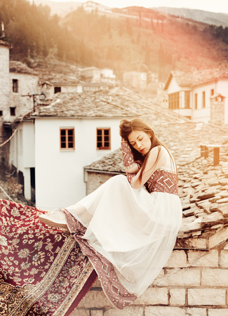 Portrait of woman in traditional dress with view to the old city of GjirokasterAlbania