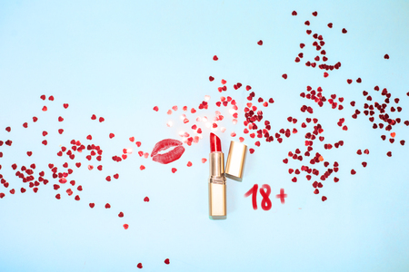 Top view red lipstick kiss on blue background with hearts confetti Stock Photo