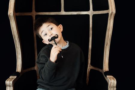 Glückliches Kind posiert mit einem falschen Schnurrbart auf schwarzem Hintergrund