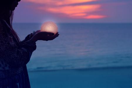 Belle fille attirante sur une plage de nuit avec du sable et des étoiles tient la lune dans ses mains Banque d'images