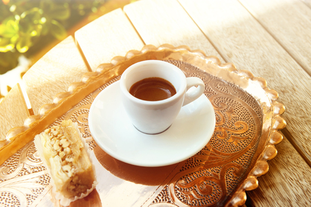 White cup of espresso coffee on wooden table background.