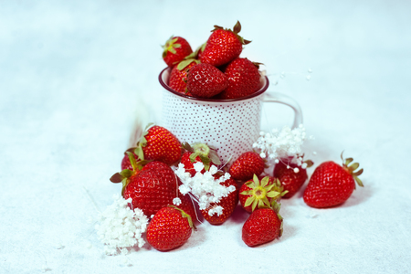 Organic red strawberries in white ceramic cup Stock Photo