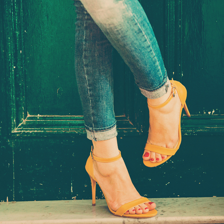 Woman wearing jeans and high heel shoes in old building
