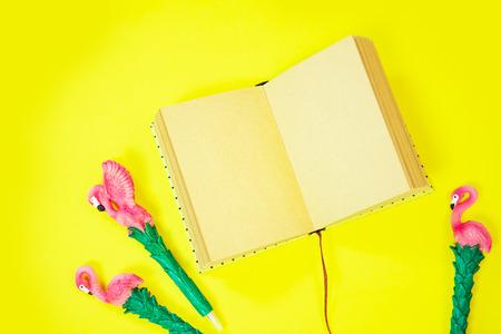 Desktop flatlay: pen with flamingo and pink paper lying vibrant yellow background Zdjęcie Seryjne