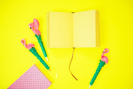 Desktop flatlay: pen with flamingo and pink paper lying vibrant yellow background Reklamní fotografie