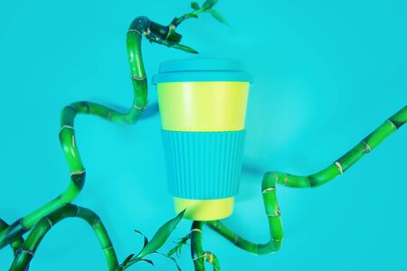 Zero waste concept. Stylish reusable eco coffee cup and green bamboo leaves.
