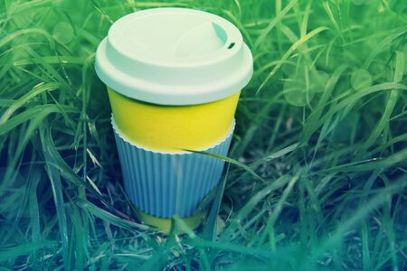 Zero waste concept. Stylish reusable eco coffee cup and green grass