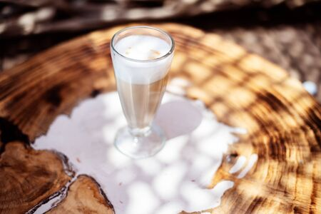 Coffee cafe latte macchiato outdoors on a rustic wooden table