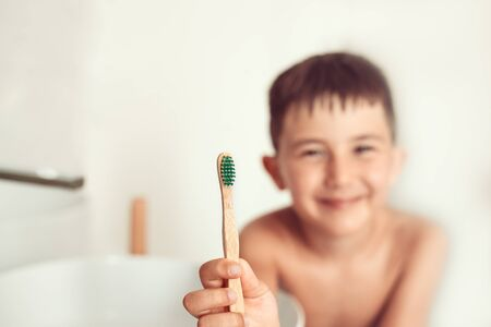 The child brushes teeth with a bamboo toothbrush. Reklamní fotografie