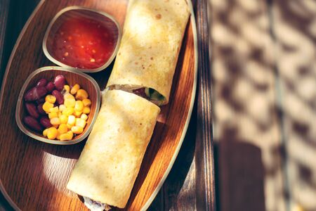 Burritos wraps with meat, beans and vegetables on wood board.