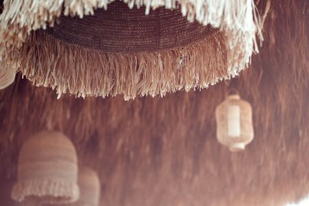 Straw cover the roof of a seaside terrace or veranda with hanging lantern