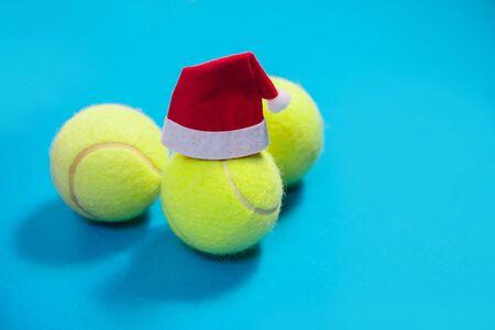 santa hat on tennis ball on blue background Фото со стока - 129324990