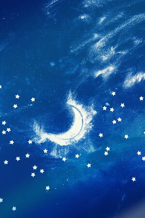 Night sky and moon: composition made of flour and candy stars on dark blue background. Vertical orientation