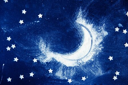 Night sky and moon: composition made of flour and candy stars on dark blue background.