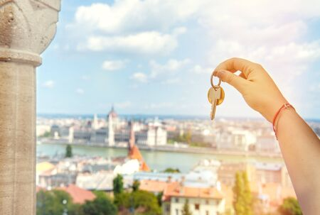 Real estate agent with house keys and European cityscape Stockfoto