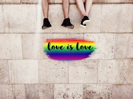 Gay pride LGBT rainbow drawn on wall, men couple feet