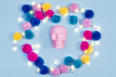Halloween human pink skull colorful knitted balls garland on pastel background Фото со стока
