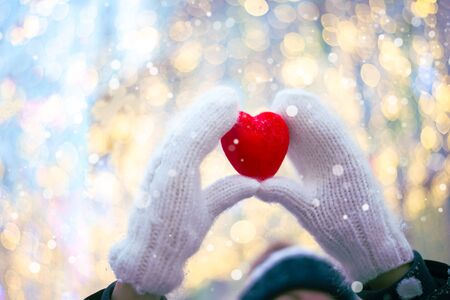 Woman hands in white knitted mittens with a red heart on a snow background. Foto de archivo