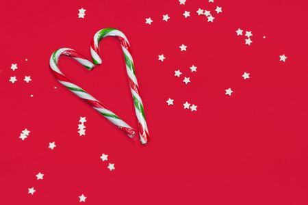 High angle shot of a group of Christmas candy canes on a red background. Zdjęcie Seryjne