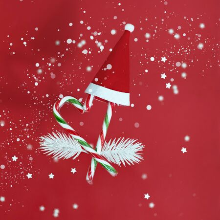 High angle shot of a group of Christmas candy canes falling on a red background.