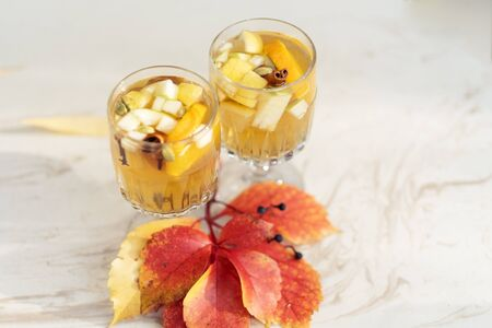 Two glasses of white mulled wine with apple, cinnamon and red autumn leaves on marble table outdoors copy space