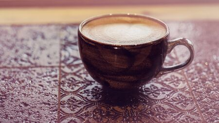 Stylish cappuccino cup close up vintage tile table