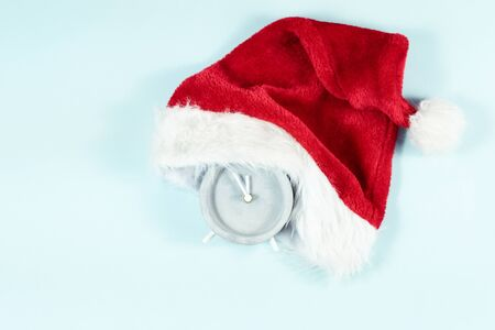 Christmas time concept. Santa Claus hat on analog retro clock showing twelve midnight top view holiday layout