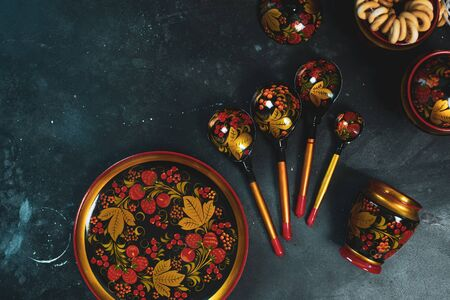 Russian khokhloma set, traditional wood painting handicraft souvenirs top view black background Stock fotó
