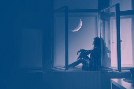 Woman sitting at the window looking at stars and the moon, Artistic Photography Stockfoto