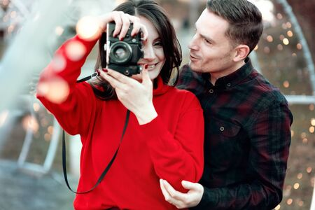 Happy couple taking photos of each other outdoors Stock Photo