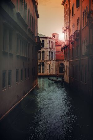 canal in Venice, Italy. Scenic sunset and architecture view colorful brick facade. Goldolier silhoette