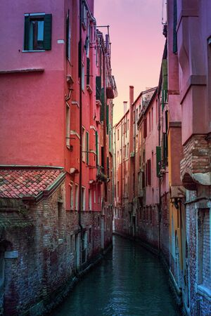 Evening canal scene at sunset, Venice, Italy. Romantic dark and vibrant cityscape. Travel and explore 免版税图像