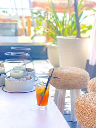 Ice tea with lemon with black straw on natural white table in summer beach bar minimal design