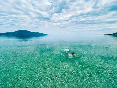 Child swimming in clean waters of Ioninan sea Albania
