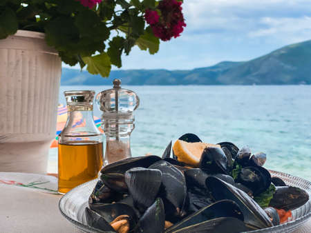 Albanian Mediterranean food fresh mussels on a table at a restaurant with a sea view. Vlora, Ionian sea summer vacation 免版税图像