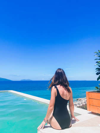 Woman sitting at a pool with sea view albania