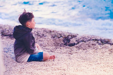little boy Child meditating on the beach