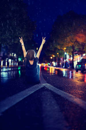 Woman sitting alone empty road during rain 免版税图像