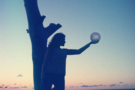 The girl holds the moon in her hands. sunset on the sea. Dreams come true. 免版税图像