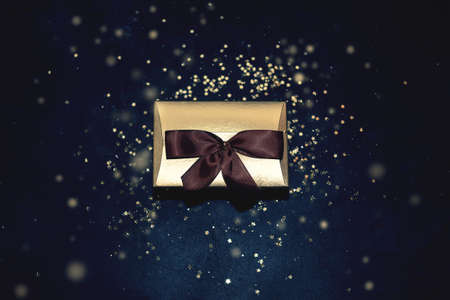 Christmas golden present with ribbon glitter sparkles background top view