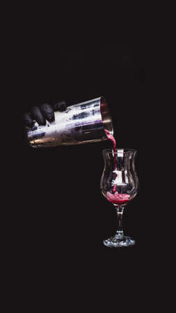 cocktail in glass with ice splashes and liquid on dark background.