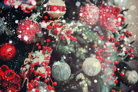red decorations hanging on Christmas tree.