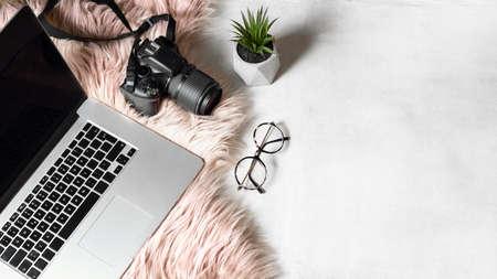 flat lay of workspace with laptop eyeglasses photo camera on white background