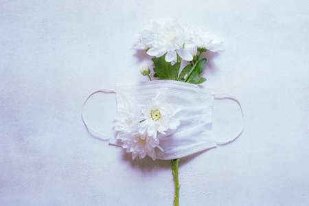 Medical concept mask and a branch of spring flowers symbol of hope.
