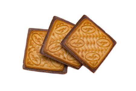 Forma quadrata del biscotto di pasta frolla nel cioccolato isolato su priorità bassa bianca.