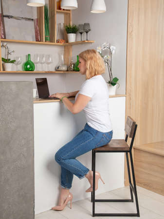 Blonde in a white T-shirt and jeans works behind a laptop
