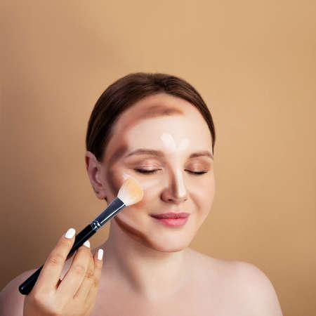 Make-up artist paints a girl. shades .Brush in hand Standard-Bild
