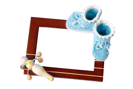 Frame with babys bootee and rattle isolated on white background Stock Photo